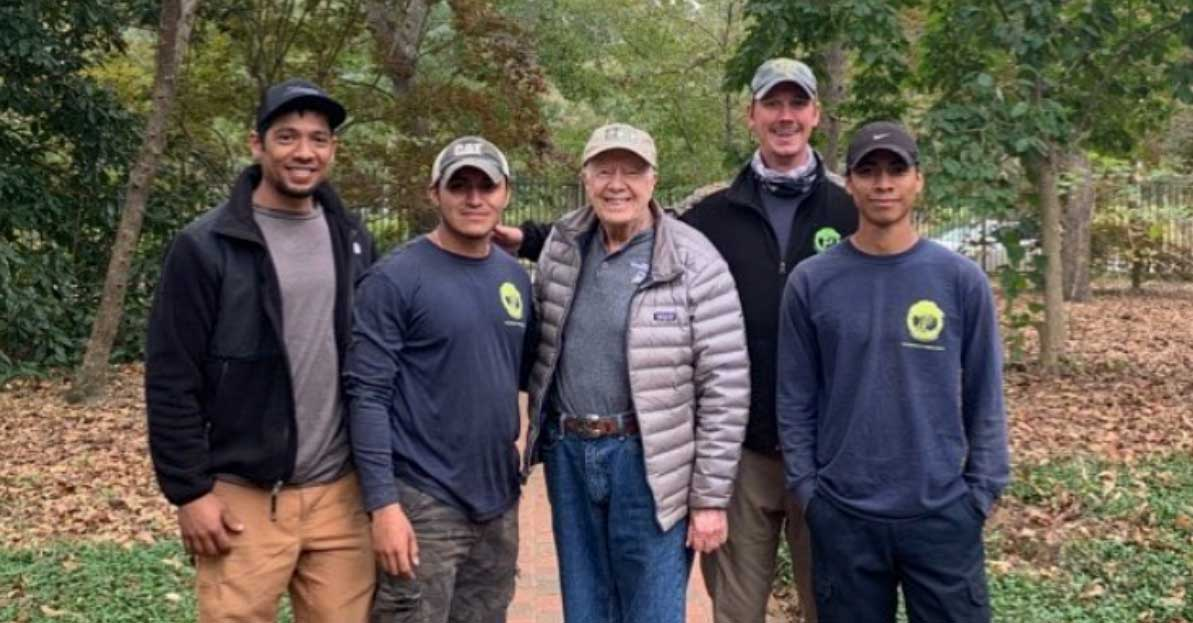 Premier Tree Solutions' employees posing for a picture with former President Jimmy Carter.