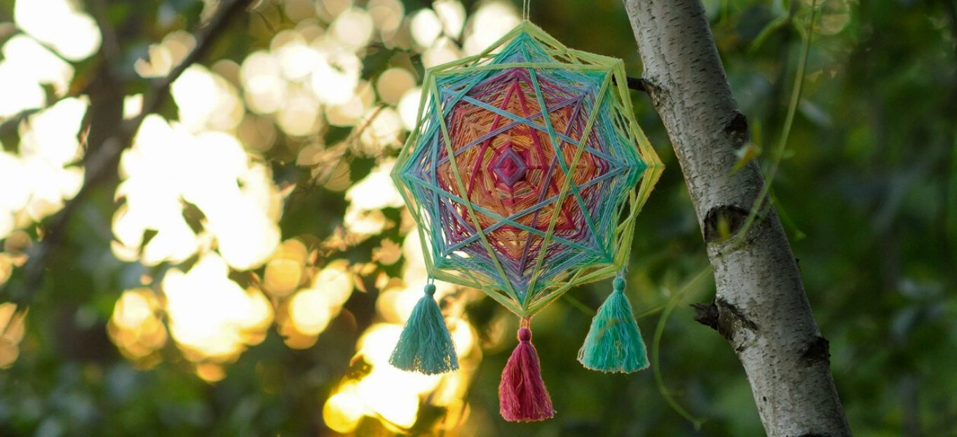 Woven colourful handcrafted yarn mandala outdoors in sunset time, highlighting Fun and Harmless Ways to Decorate Your Trees.